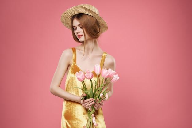 女性の手に花のピンクの花束黄金のドレスの豪華な装飾