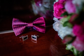 Pink bow tie, cufflinks and wedding bouquet lie on wooden table