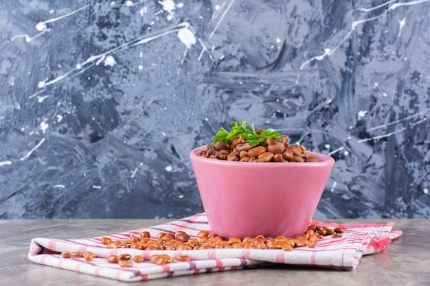 Pink bowl of boiled beans with tablecloth on marble surface.