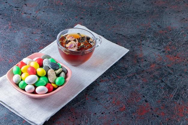 Ciotola rosa di caramelle colorate e tazza di tè nero su superficie scura.