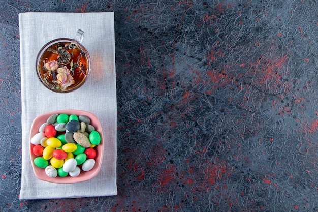 Pink bowl of colorful candies and cup of black tea on dark surface.
