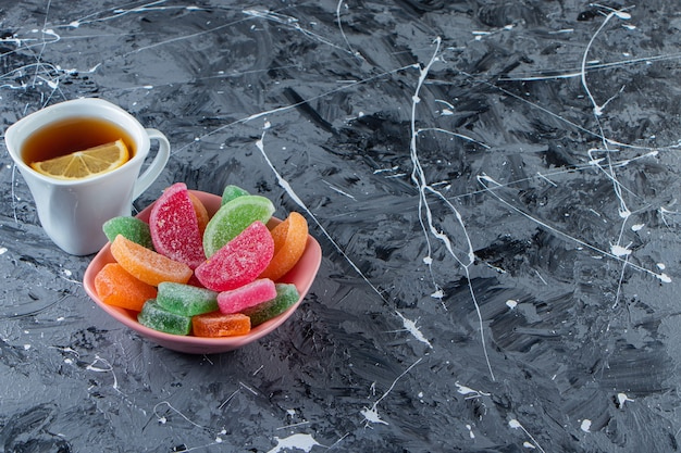 Pink bowl of colorful marmalades with cup of hot tea on marble surface.