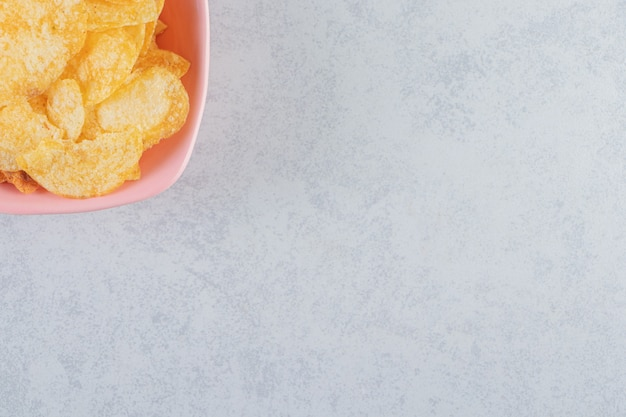 Ciotola rosa di deliziose patatine croccanti su sfondo di pietra.