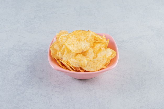 Pink bowl of delicious crunchy chips on stone background.