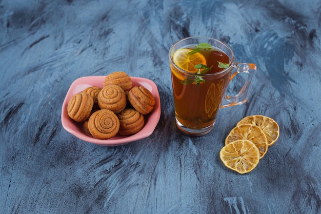 Pink bowl of mini cinnamon cakes with glass of tea on stone surface.