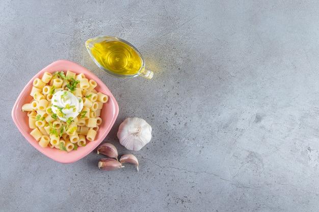 石の背景にオリーブオイルとおいしいゆでパスタのピンクのボウル。