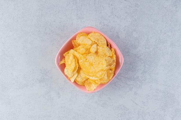 돌 배경에 맛있는 바삭바삭한 칩의 분홍색 그릇.