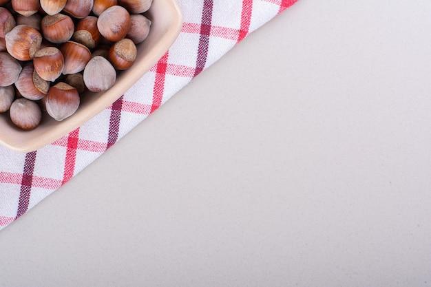 白い背景の上に配置された殻付き有機ヘーゼルナッツのピンクのボウル。高品質の写真