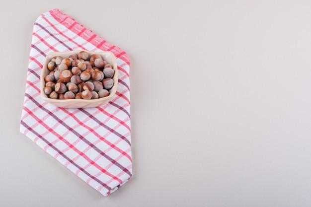 껍질을 벗긴 유기농 헤이즐넛의 분홍색 그릇은 흰색 배경에 놓여 있습니다. 고품질 사진