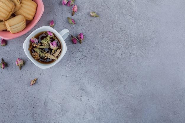 Розовая миска сладкого печенья и чашка горячего чая на каменном фоне.