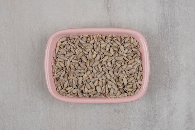 Ciotola rosa di semi di girasole arrostiti su fondo di marmo.