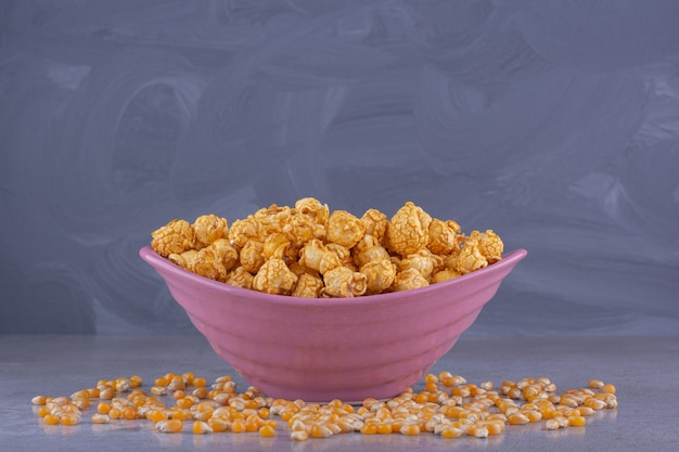 Pink bowl of salty popcorn on stone surface