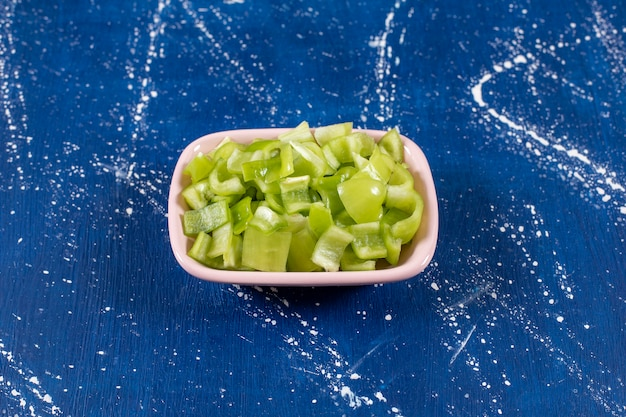 Ciotola rosa di peperoni verdi a fette su superficie di marmo