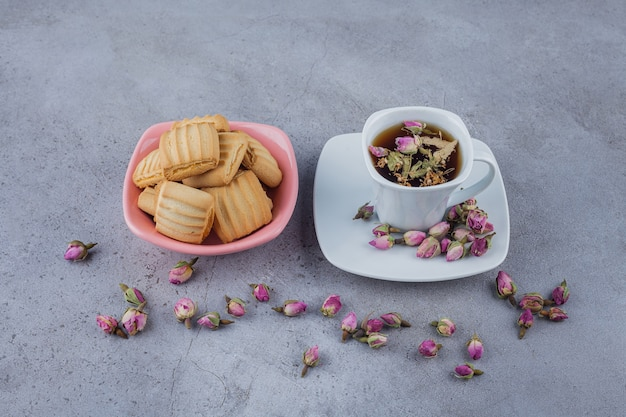 Pink bowl of sweet biscuits and cup of hot tea on stone surface.