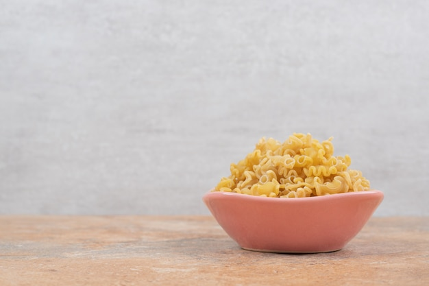 A pink bowl of unprepared macaroni on marble background. high quality photo