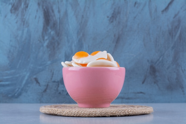 A pink bowl with sweet jelly-fried eggs on gray surface