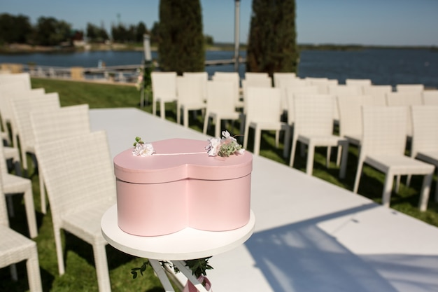 Pink box for presents in the shape of a heart is on the table, wedding outdoor on the lawn