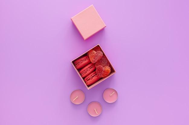 마멀레이드와 마카롱이있는 분홍색 상자와 분홍색 테이블에 아름다운 장미