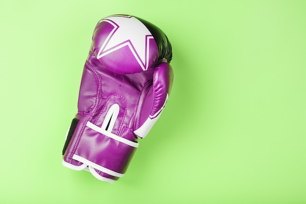 Pink boxing glove on a green background