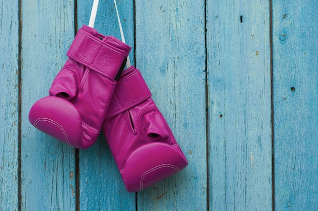 Pink boxing gloves on blue cracked wooden surface