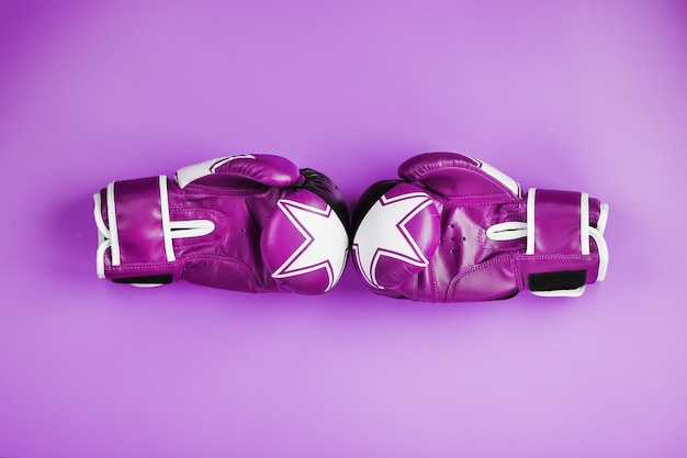 Pink boxing gloves on a pink background, free space.