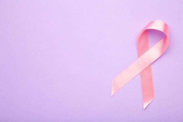 紫色の背景にピンクの乳がんリボン。