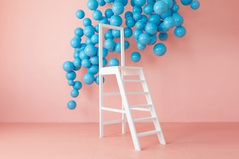 Pink bright studio interior with white ladder and hanging blue balls.