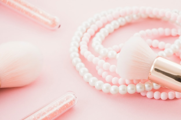 Pink brushes and pearl necklace