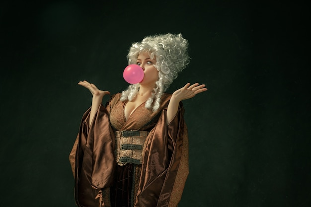 Pink bubble gum. portrait of medieval young woman in brown vintage clothing on dark background. female model as a duchess, royal person. concept of comparison of eras, modern, fashion, beauty.