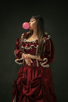 Pink bubble gum. portrait of medieval young woman in red vintage clothing standing on dark background. female model as a duchess, royal person. concept of comparison of eras, modern, fashion, beauty.