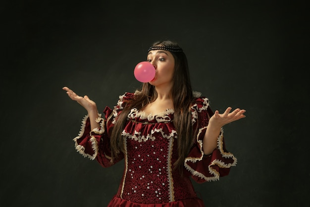 Pink bubble gum. portrait of medieval young woman in red vintage clothing standing on dark background.