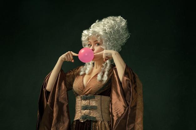 ピンクの風船ガム。暗い背景に茶色のヴィンテージの服を着た中世の若い女性の肖像画。公爵夫人、王室の人としての女性モデル。時代、現代、ファッション、美しさの比較の概念。