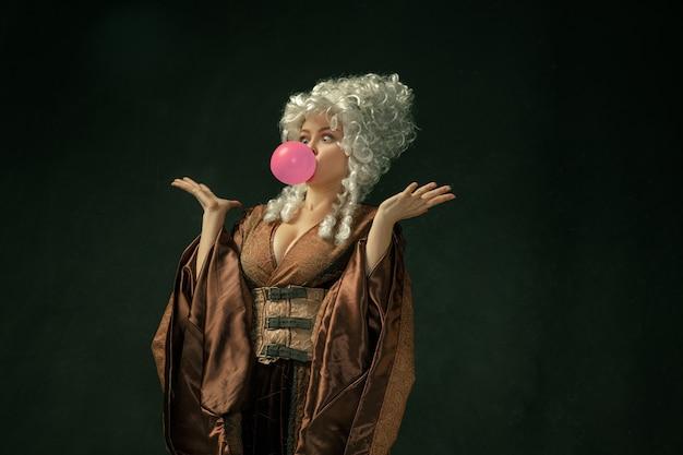 핑크 풍선 껌. 어두운 배경에 갈색 빈티지 의류에서 중세 젊은 여자의 초상화. 공작 부인, 왕실 사람으로 여성 모델. 시대, 현대, 패션, 아름다움의 비교 개념.