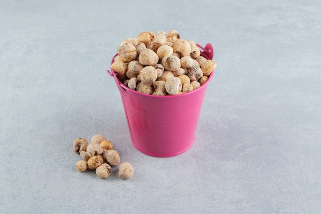 A pink bucket full of delicious dried fruit .