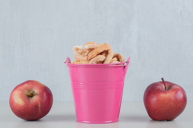 A pink bucket full of dried apple with two fresh apples .