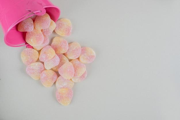 Un secchio rosa pieno di caramelle di gelatina a forma di cuore.