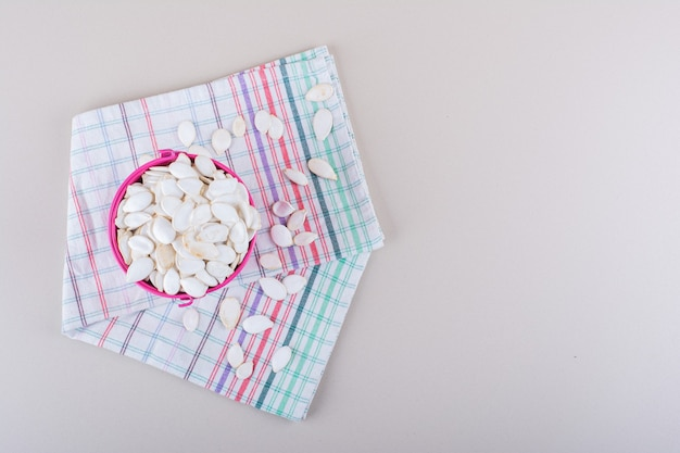白い背景の上の有機カボチャの種でいっぱいのピンクのバケツ。高品質の写真