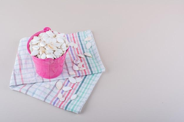 Secchio rosa pieno di semi di zucca organici su sfondo bianco. foto di alta qualità