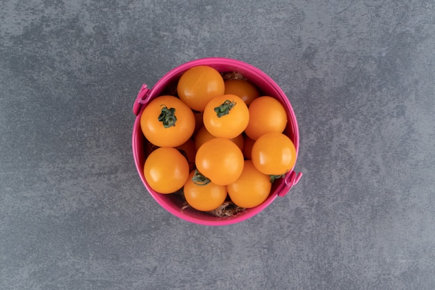 A pink bucket full of ripe tasty yellow cherry tomato