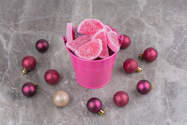 A pink bucket full of sweet marmalades with red christmas balls on marble background.