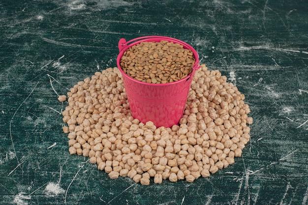 大理石のテーブルのエンドウ豆の輪に種子のピンクのバケツ。