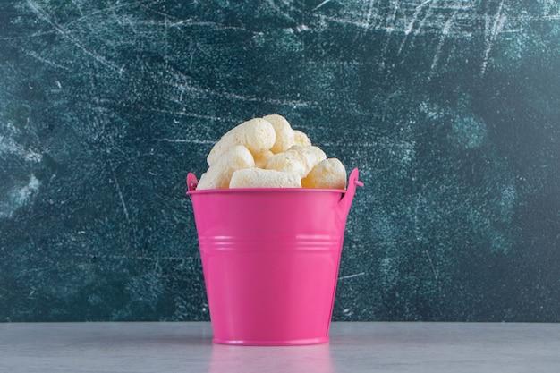 Pink bucket of sweet corn sticks on stone background.