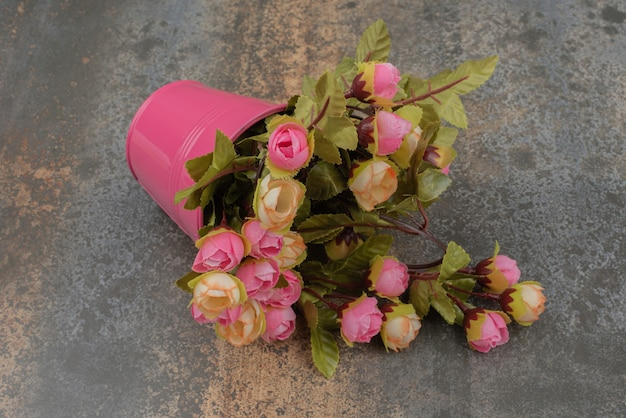 A pink bucket with bouquet of flowers on marble surface.
