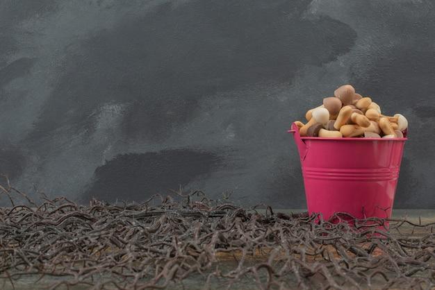 大理石の表面の木にキノコとピンクのバケツ。