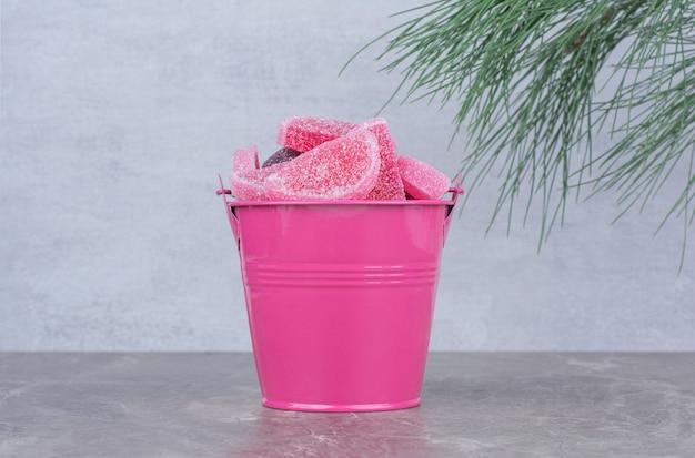 Secchio rosa con marmellata di zucchero su sfondo marmo.
