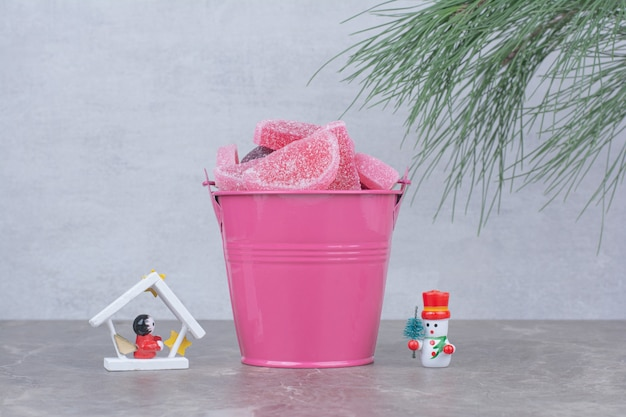 Pink bucket with sugar marmalade on marble background.
