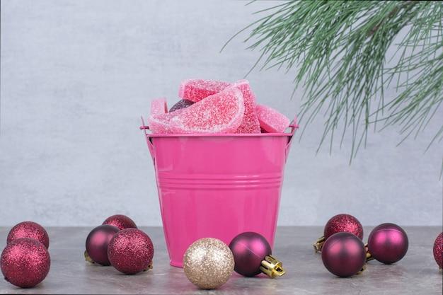 대리석 배경에 설탕 마멀레이드와 핑크 양동이.