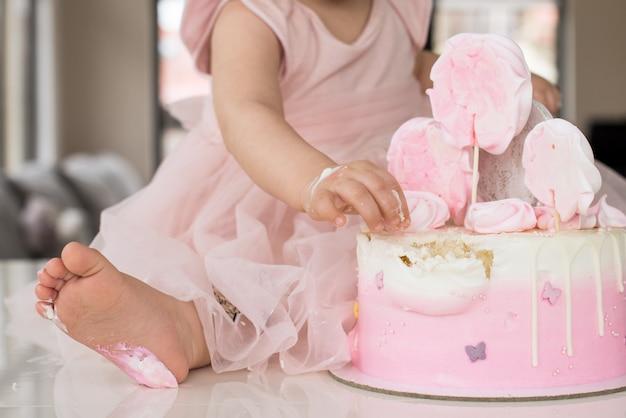 핑크 케이크. 소녀의 첫 생일, 망가진 케이크, 깨진 마시멜로, 아기 손과 다리.