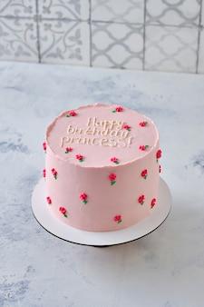 小さなお姫様や大きなお姫様のためのピンクのケーキ。小さなクリーム色の花で飾られたトレンディな韓国風ケーキ。