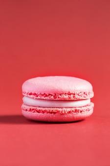 Розовый торт macaron или миндальное печенье на красной стене. разноцветное миндальное печенье. французский макарун